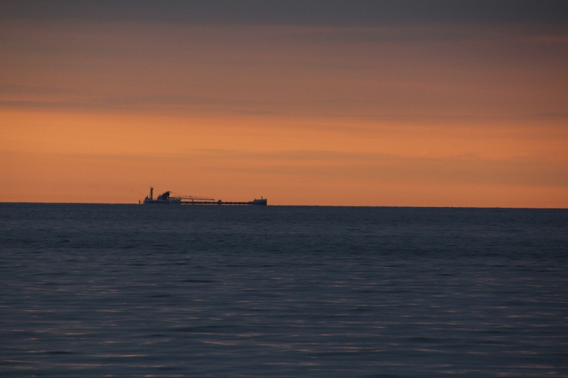 Fishing boat chugging along the horizon at sunrise.